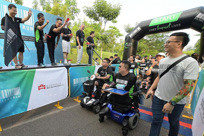 Second Minister for Home Affairs Desmond Lee (left, with a tattoo sleeve) flagging off the run yesterday. With him on stage was Berita Harian Editor Saat Abdul Rahman (second from left) and New Charis Mission executive director Don Wong (third from l