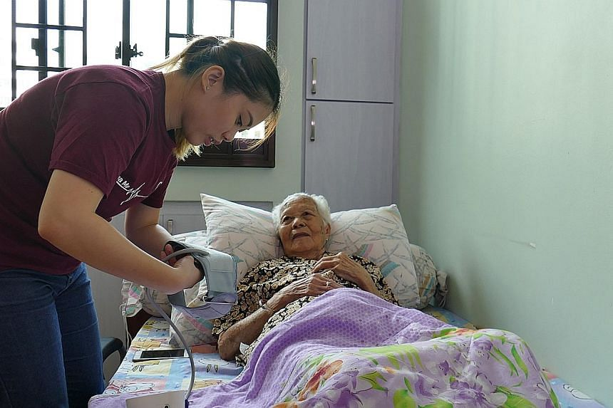 A Jaga-Me home care nurse assisting a patient in Bukit Panjang. The social enterprise charges $550 a day for 24-hour care, but recently started Project Going Home to offer free nursing services to financially needy patients who have been given a term