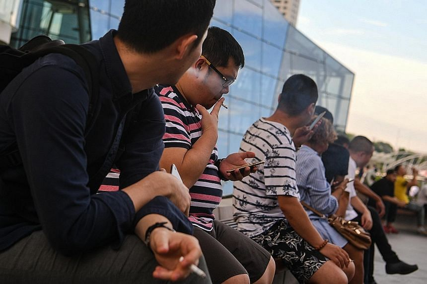 People having a smoke at Marina Bay Sands. There has been a number of changes to Singapore's anti-smoking policies as the Government seeks to get people to quit the habit. Although the number of adults smoking fell progressively from 23 per cent in 1