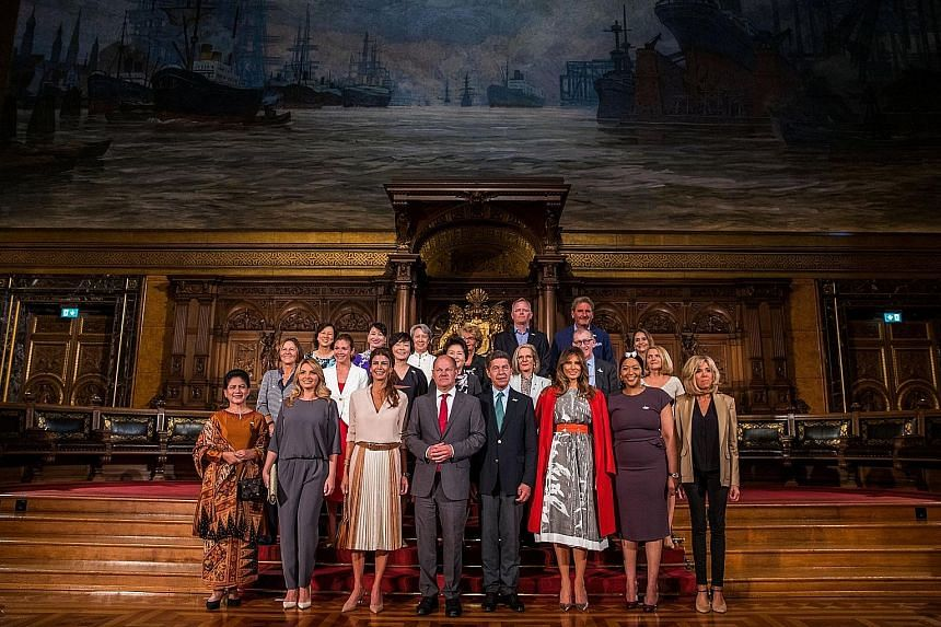 Hamburg Mayor Olaf Scholz (fourth from left) with the partners of G-20 summit participants during a tour of the German city's 17th-century town hall yesterday. With him in the front row are (from far left) Mrs Iriana Widodo, wife of the Indonesian Pr