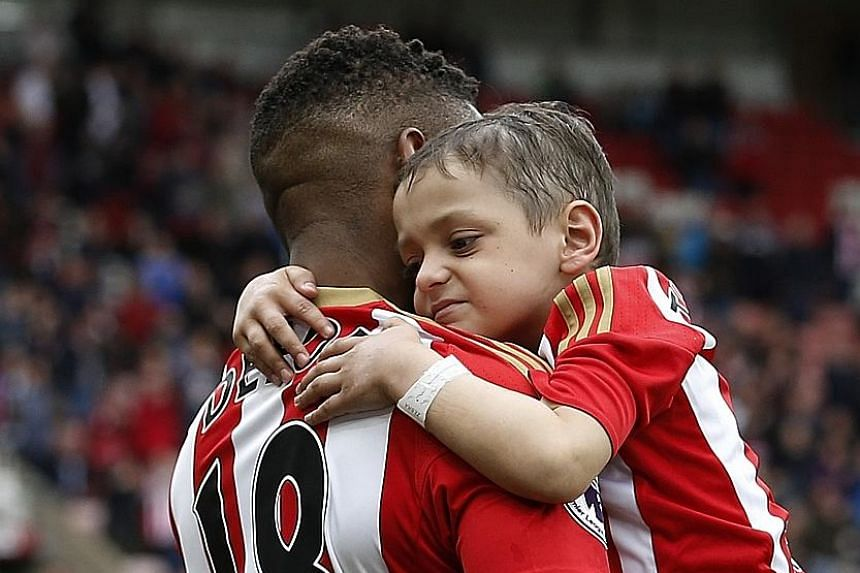 Sunderland's Jermain Defoe walks out with Bradley Lowery before the match against Swansea City on May 13. The six-year-old's death was announced by his family on Friday. His plight touched people all round the world and he received 250,000 Christmas
