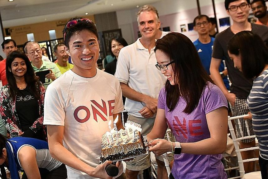 Left: Mok Ying Ren, who turned 29 on Thursday, is surprised with a belated birthday cake. Below: About 30 participants warm up with Singapore marathoner Mok (right, in blue) at Suntec City.