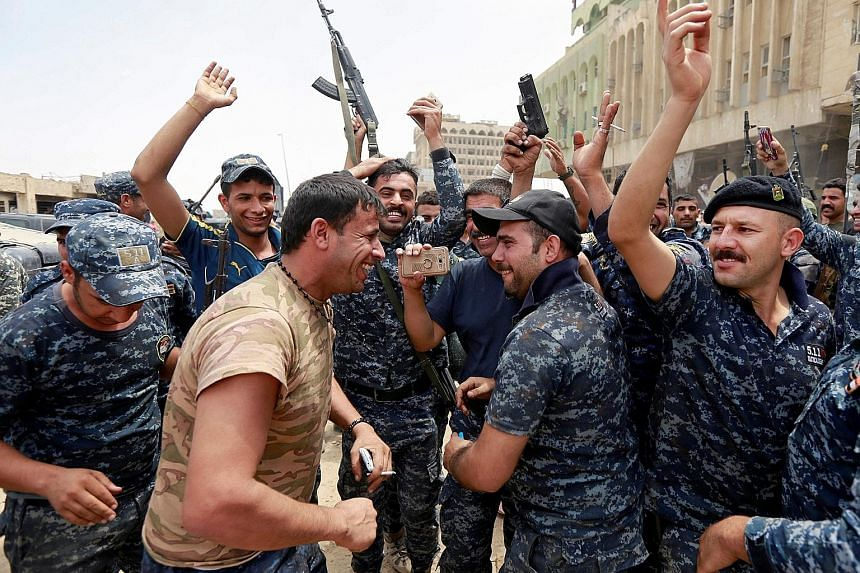 Officers from the Iraqi Federal Police celebrating in the Old City of Mosul, without waiting for a formal victory announcement to be made.