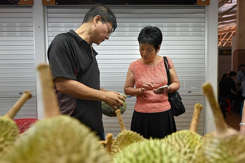 Mr Steven Shui Poh Sing, owner of Ah Seng Durian at Ghim Moh Market, cracking open a durian for a customer. Durian vendors said business may pick up in the coming weeks - prices are expected to fall slightly as the current season approaches its peak.