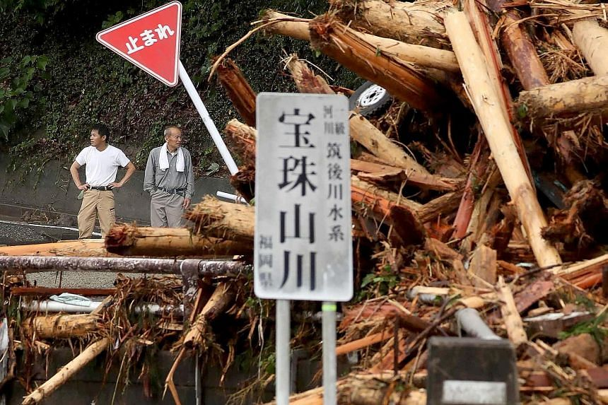 Residents surveying the damage left behind by torrential rain and flooding in Toho, Fukuoka prefecture, yesterday.