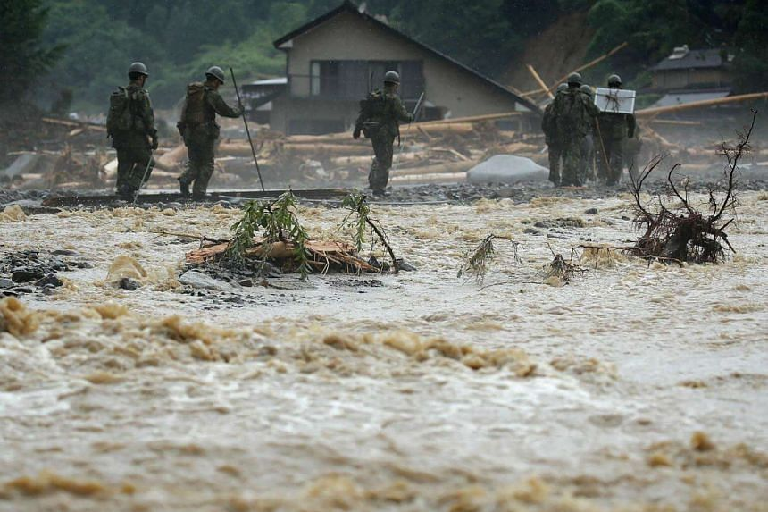 Defense forces soldiers walk beside a river during a search operation for missing poeple in a flooded area in Asakura.