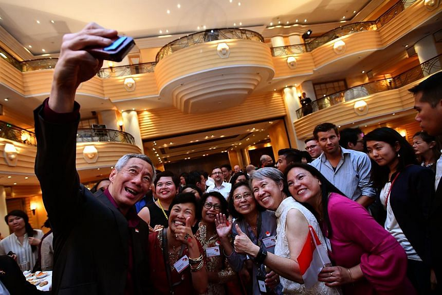 (From left) Prime Minister Lee Hsien Loong taking a photograph with Mrs Daliyana Ravi, Mrs Flora Tan-Makowski, Mrs Hatijah Nuss, Mrs Amy Kiesgen, Mrs Lee and Madam Kim Goh Huey Chyiy at Bayerischer Hof Hotel in Munich on July 9, 2017.