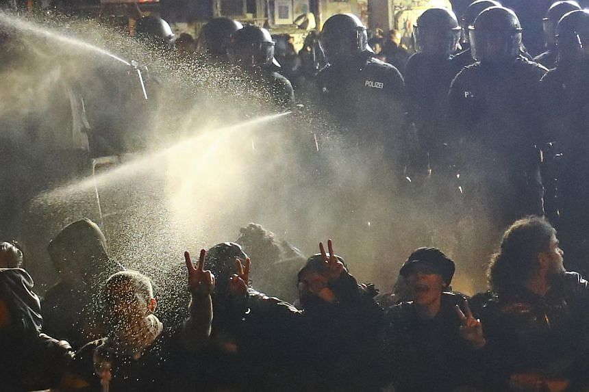 German riot police using tear gas to disperse protesters in the Schanze district in Hamburg on July 9, 2017.