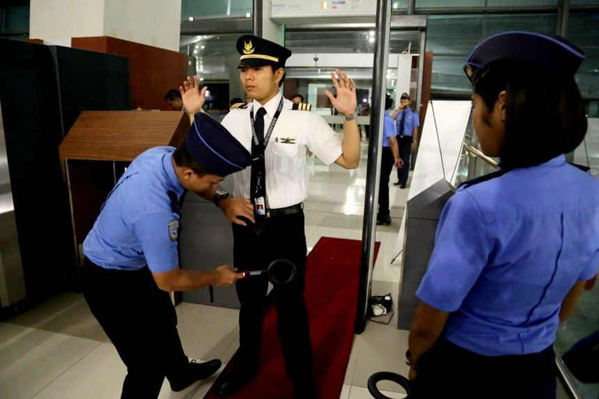 Security officers conducting a body search on a staff member at Terminal 3 of Soekarno-Hatta International Airport.