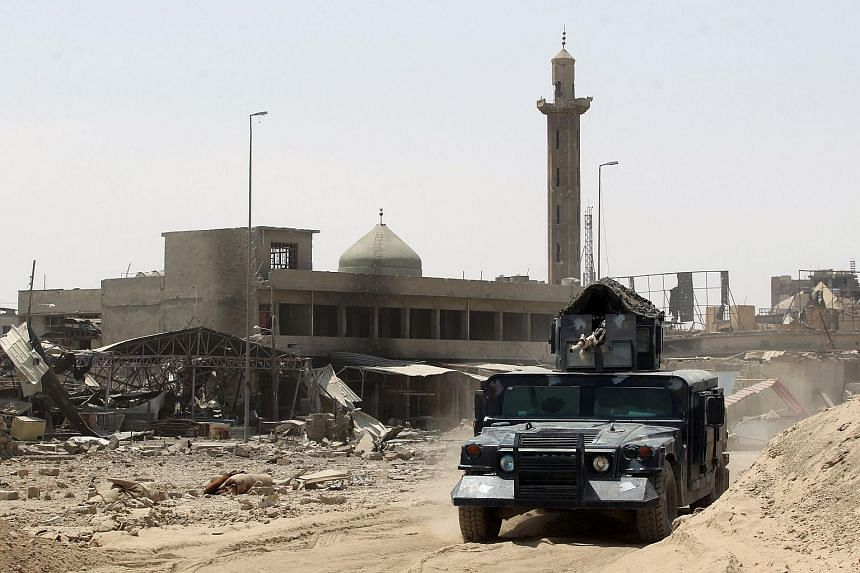Iraqi forces driving their vehicle past a mosque in Mosul's Old City on July 9, 2017.