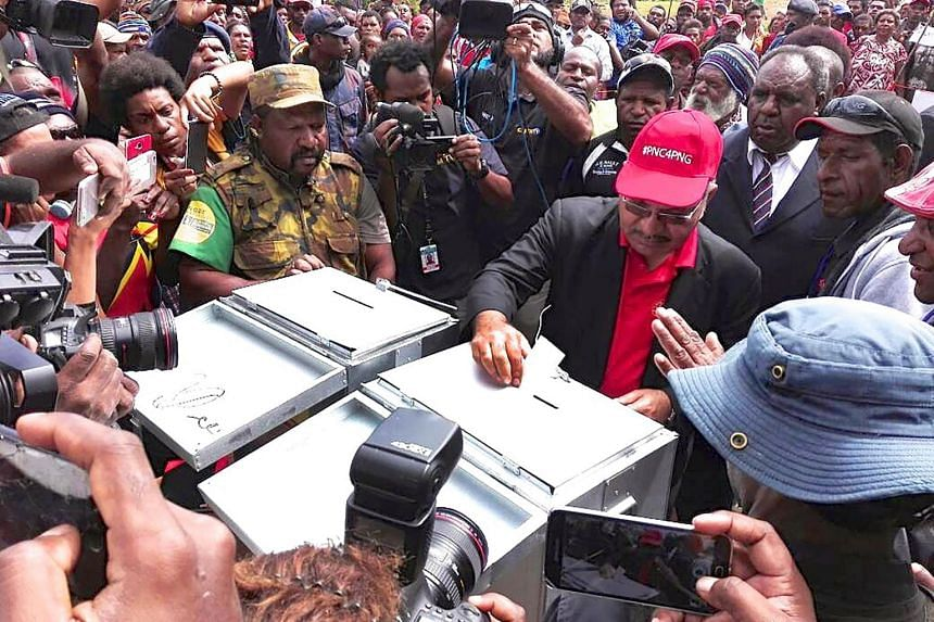 Papua New Guinea Prime Minister Peter O'Neill (in red cap) voting in the village of Kawo on July 2, 2017.