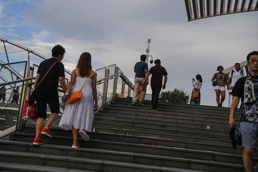 A couple holds hands as they walk up the Helix Bridge at Marina Bay Sands.