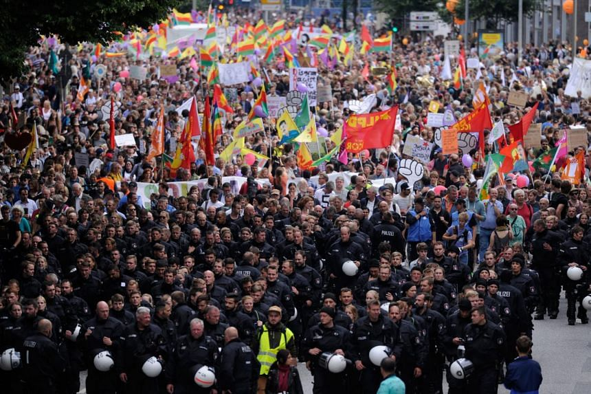 """Policemen walk in front of demonstrators carrying flags and banners as they take part in the """"Solidarity without borders instead of G20"""" protest in Hamburg on July 8, 2017."""