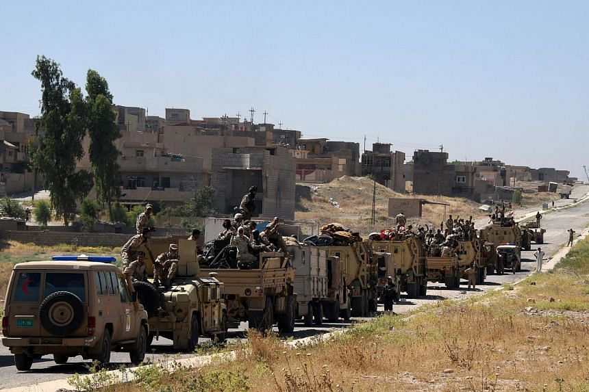 Iraqi government forces drive down a road leading to Tal Afar on June 9, 2017, during ongoing battles to retake the city from Islamic State (IS) group fighters.