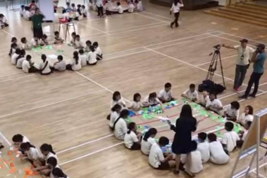The Primary 4 pupils from Boon Lay Garden Primary School were building houses of cards on large cardboard canvas that were resting on the laps of their peers.