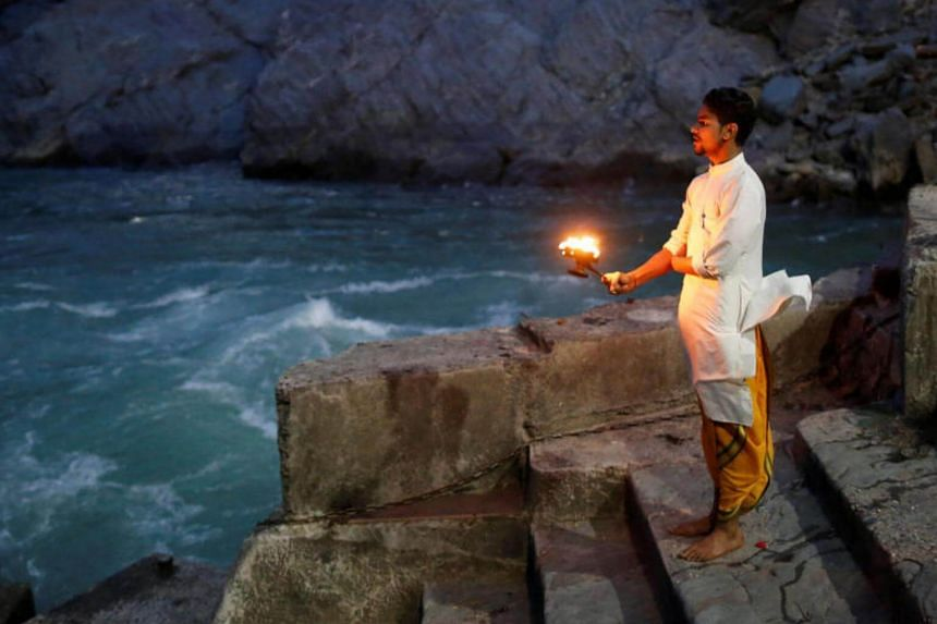 Lokesh Sharma, 19, a Hindu priest, performs evening prayers on the banks of the river Ganges in Devprayag, India, on March 28, 2017.