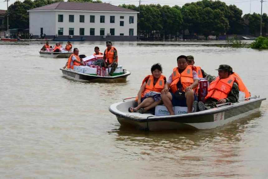 Police transporting relief goods for people trapped in flooded areas in Yuanjiang, Huna on July 4, 2017.