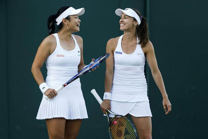 Martina Hingis of Switzerland (right) and Yung-Jan Chan of Chinese Taipei during their ladies doubles match against Xenia Knoll of Switzerland and Alize Cornet of France in London, Britain, on July 5, 2017.