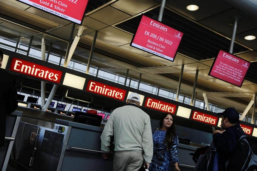 Travelers wait at an Emirates Airlines ticket desk at JFK International Airport in New York, US, on March 21, 2017.
