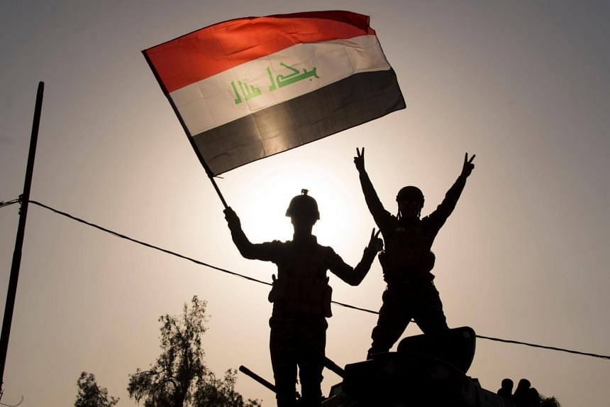 Iraqi Federal Police officers waving the Iraqi flat as they celebrate in the Old City of Mosul on July 9, 2017.