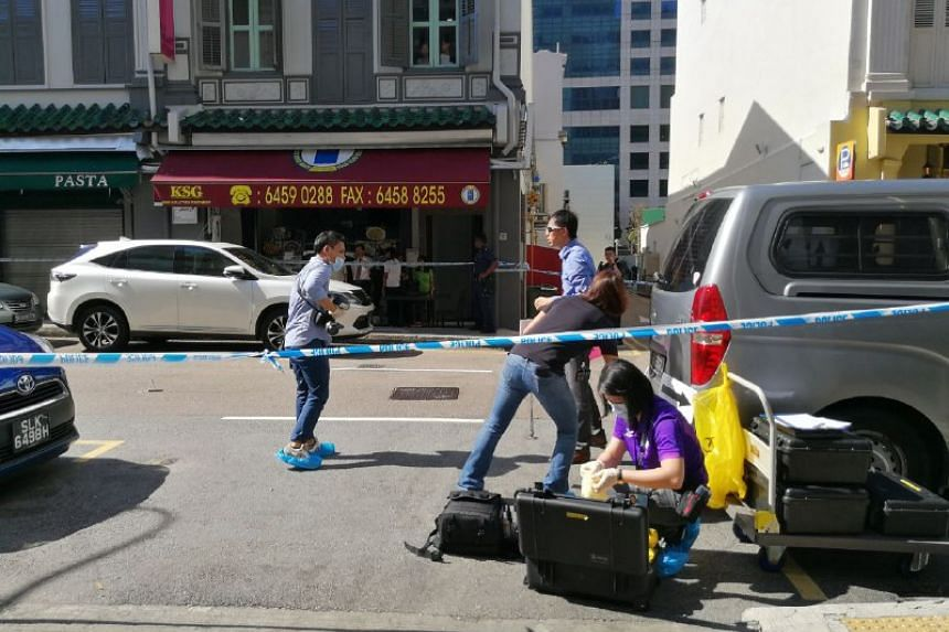 Investigators marking out the scene at Boon Tat Street.