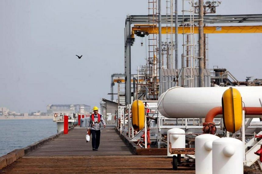 An Iranian labourer walking the platform of the oil facility in the Khark Island, on the shore of the Gulf.