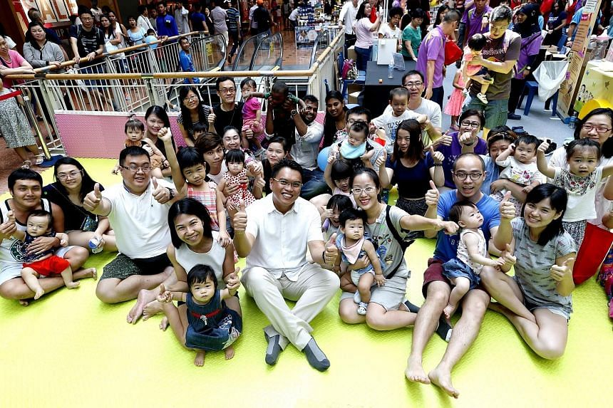Mr Patrick Tay (centre), adviser to Boon Lay grassroots organisations, with parents at the programme's launch yesterday.
