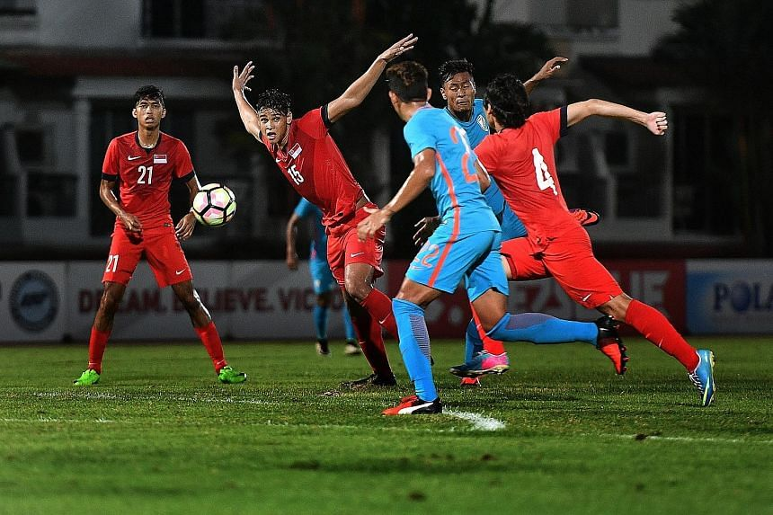 Young Lions' Irfan Fandi (No. 15) and Jordan Chan (No. 4) competing for the ball against India's U-23 side at the Choa Chu Kang Stadium. Both teams play again on Wednesday.