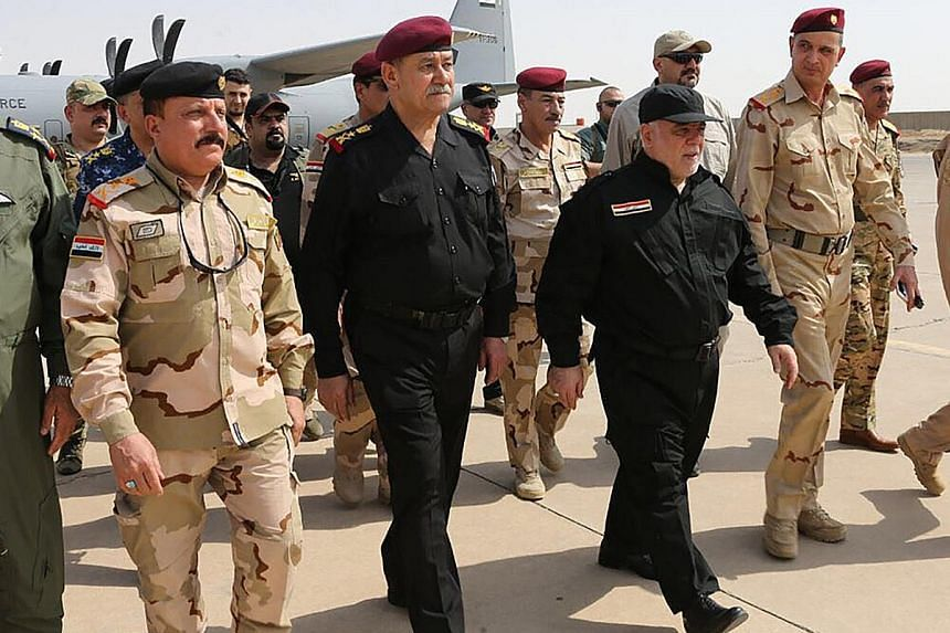 Iraqi Prime Minister Haider al-Abadi (in black, right) arriving in Mosul yesterday, where he celebrated victory over ISIS. Iraqi forces in Mosul yesterday. Retaking the city marks a major blow against ISIS, which is also under siege in the Syrian str