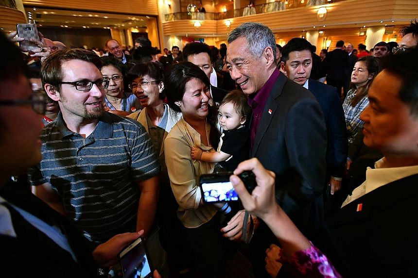 Prime Minister Lee Hsien Loong meeting guests at a National Day reception in Munich yesterday. Among them were Singaporean psychologist Anna Costa, 32, her German husband, 35-year-old engineer Florian Klotz (far left), and their 10-month-old son Imma