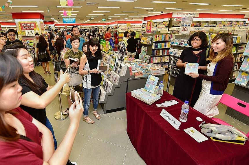 Geography teacher Rama Anant Kulkarni posing with columnist Sumiko Tan during the book signing at Popular Bookstore in nex mall yesterday. Sundays With Sumiko, published by Straits Times Press, compiles 74 columns written by Ms Tan from 1994 to last