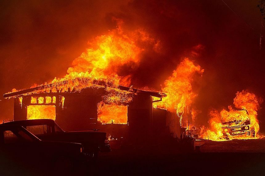A car and house are engulfed in flames as a fire burns through a residential area in Oroville, California. Searing temperatures and parched land fuelled dozens of blazes in the West and South-west of the United States. There were 40 uncontained large