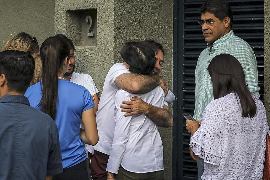 Ms Antonieta de Lopez, the mother of opposition leader Leopoldo Lopez, being hugged by a relative as they wait outside Mr Lopez's residence after he was released from the Ramo Verde military prison and placed under house arrest, in Caracas, Venezuela