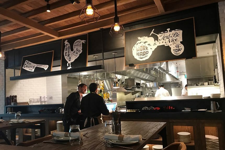 Quirky chicken sketches above the open-concept kitchen add a whimsical touch to the restaurant.