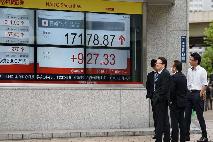A pedestrian walks past an electronic stock board outside a security firm in Tokyo, Japan.