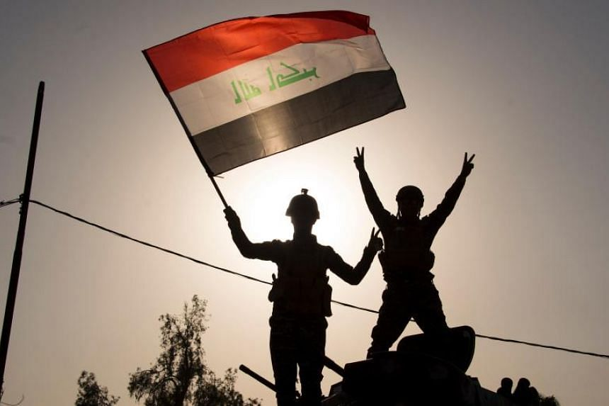 "Iraq's federal police members waving the country's national flag as they celebrate in Mosul on July 9, 2017, after the government's announcement of the ""liberation"" of the embattled city."