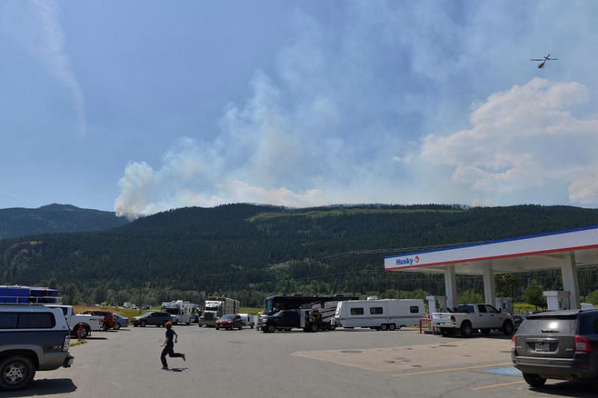 A helicopter returns from surveying some of the numerous wildfires as people fill up gas and food at a service station in Little Fort, British Columbia, Canada, on July 9, 2017.