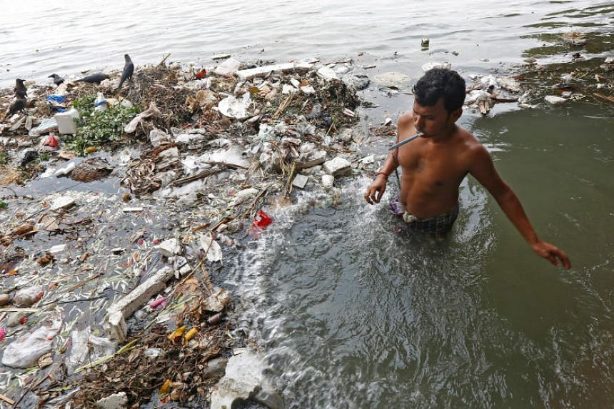 A man brushes his teeth as he stands in the polluted water of river Ganga in Kolkata, India May 23, 2017.