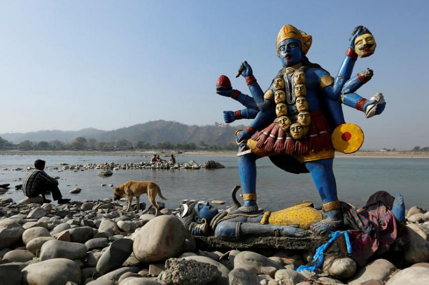 A man sits next to a damaged idol of Hindu goddess Kali which was taken out after its immersion in the river Ganges in Haridwar, India, March 29, 2017.