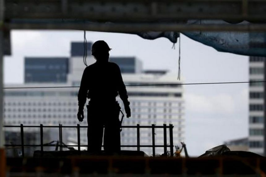 A worker stands in the shell of a building at a construction site in Tokyo.