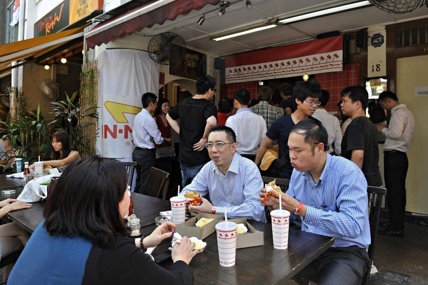 The early birds who queued successfully for the American burger chain In-N-Out burgers enjoying their meal.