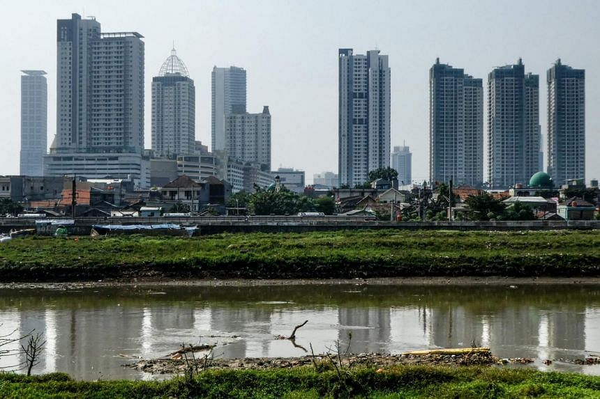 Buildings of the Jakarta skyline are seen past shantyhouses on July 4, 2017.