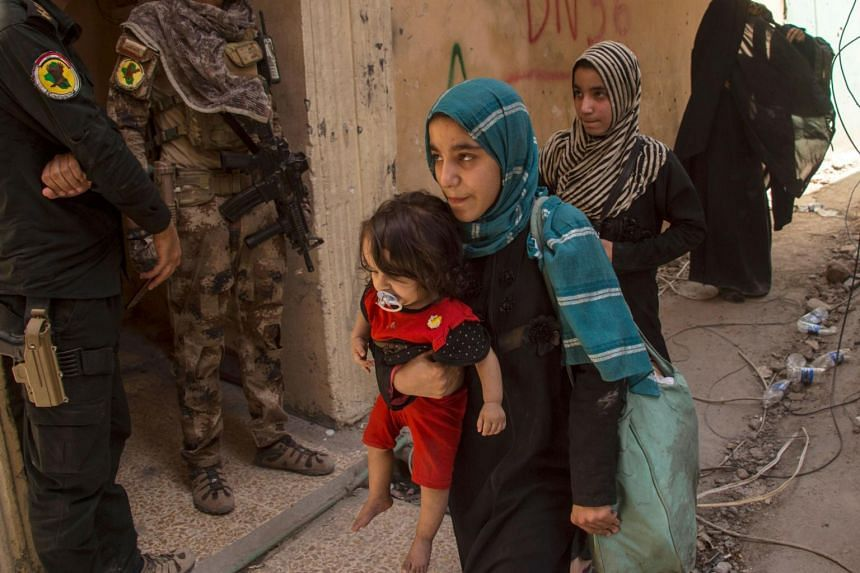 Civilians flee as members of Iraq's Counter-Terrorism Service advance in the Old City of Mosul, on July 5, 2017.
