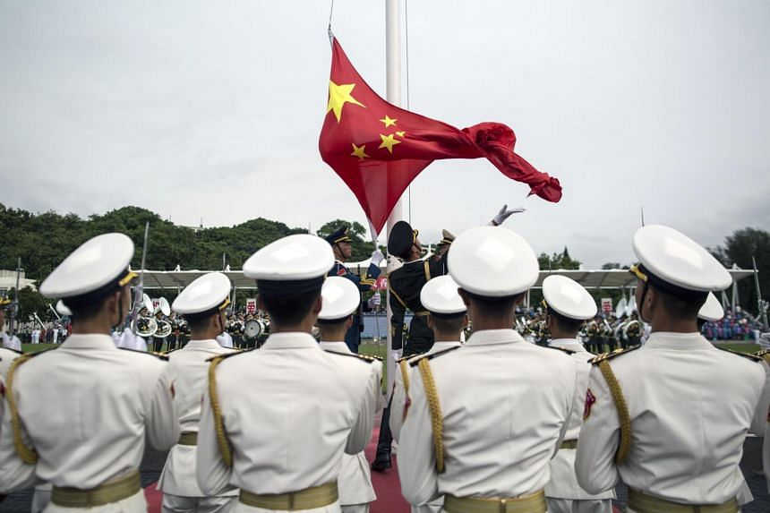 People's Liberation Army soldiers participate in a flag raising ceremony during an open day at the PLA navy base in Hong Kong, on July 8, 2017.