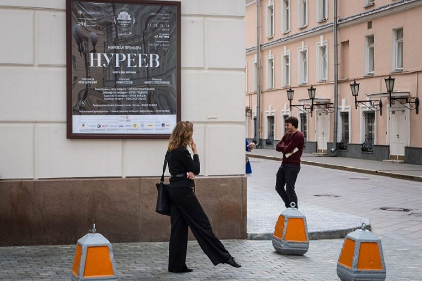 People stand outside the Bolshoi Theatre next to a plaque announcing the Nureyev ballet premiere in Moscow on July 9, 2017.
