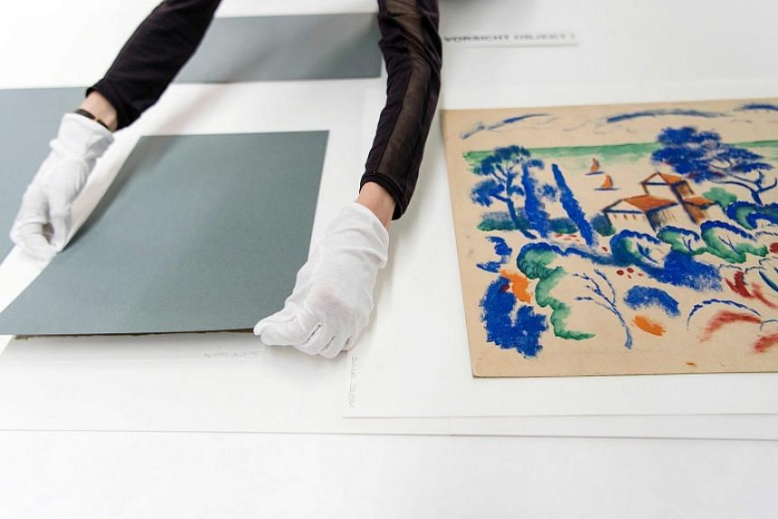 An official diplays the Landschaft mit Segelbooten, a gouache by German expressionist August Macke, from the estate of German collector Cornelius Gurlitt during a press preview at the Museum of Fine Arts Bern on July 7, 2017.