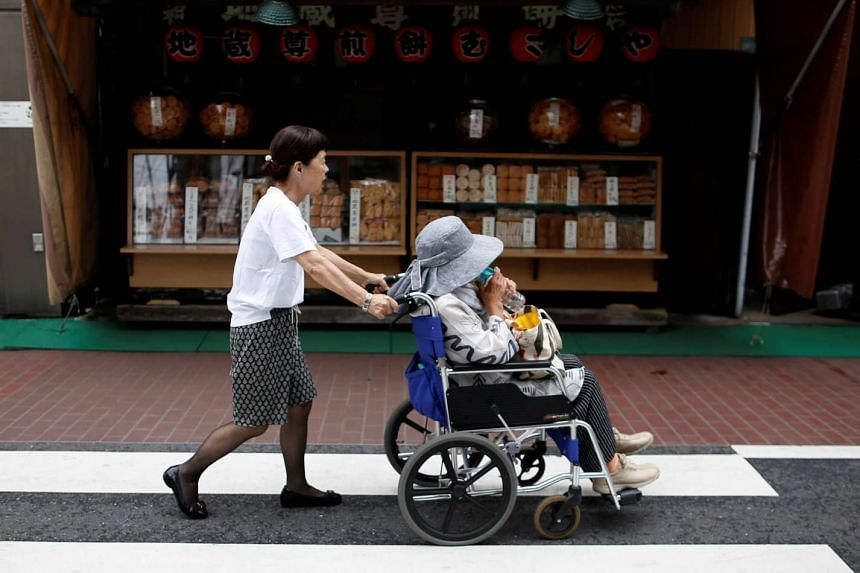 An elderly person in a wheelchair is aided by a woman as they past the street in Sugamo district, an area popular among the Japanese elderly, in Tokyo, Japan June 30, 2017.