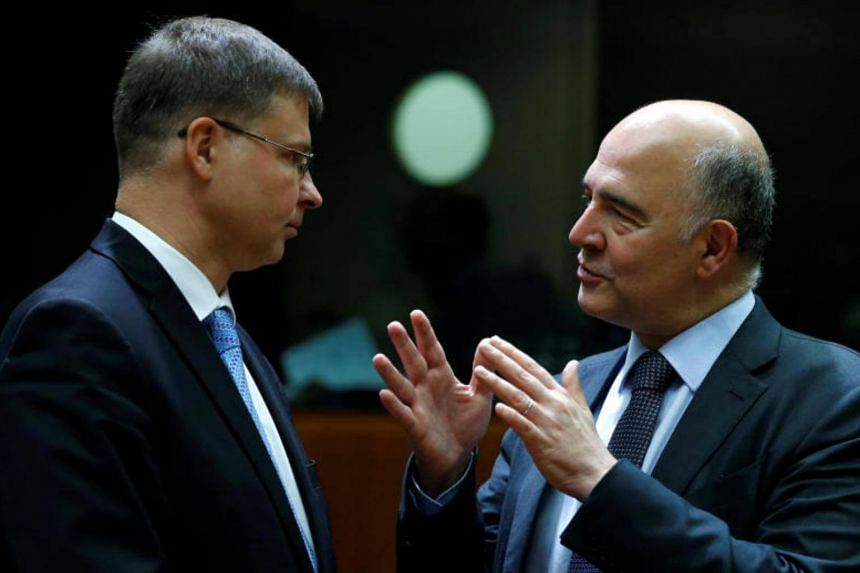 European Commission Vice-President Valdis Dombrovskis and European Economic and Financial Affairs Commissioner Pierre Moscovici attend an European Union finance ministers meeting in Brussels, Belgium, on July 11, 2017.