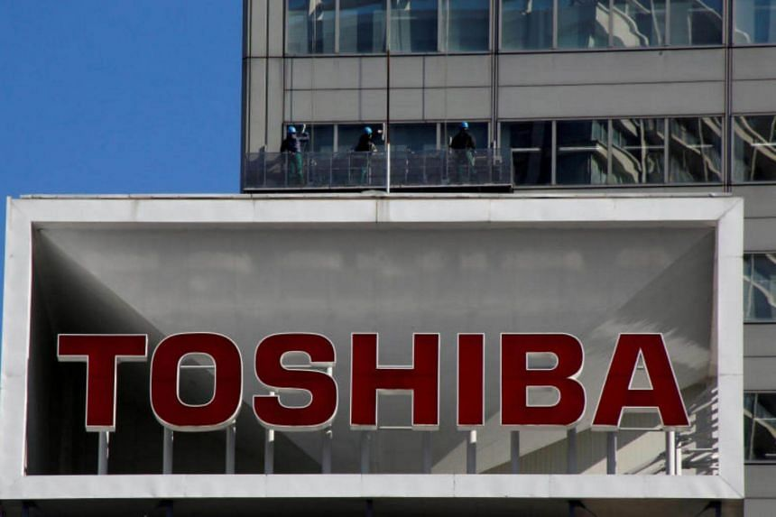 The logo of Toshiba Corp is seen as window cleaners work on the company's headquarters in Tokyo, Japan, on Feb 14, 2017.