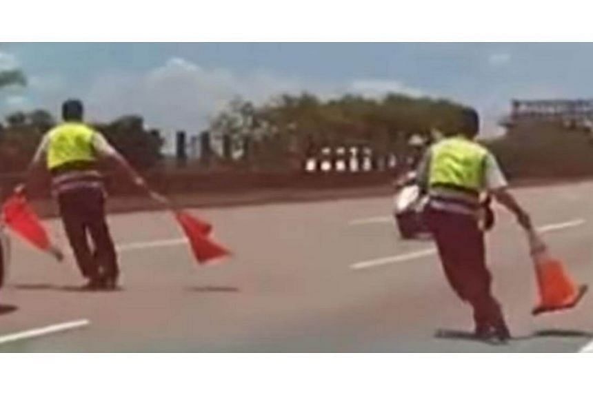 One police officer holds up traffic cones and another hurls his cone to stop a 65-year-old man riding against traffic on a highway.